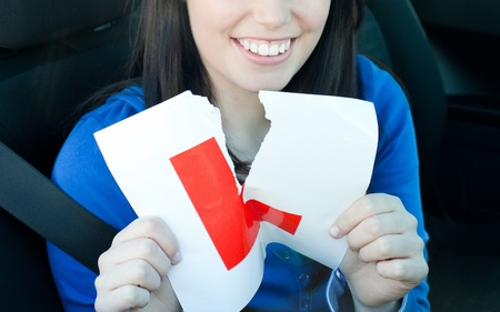Charming teen girl sitting in her car tearing a L-sign photo