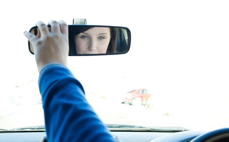 mirror face: Caucasian woman looking in the rear-view mirror