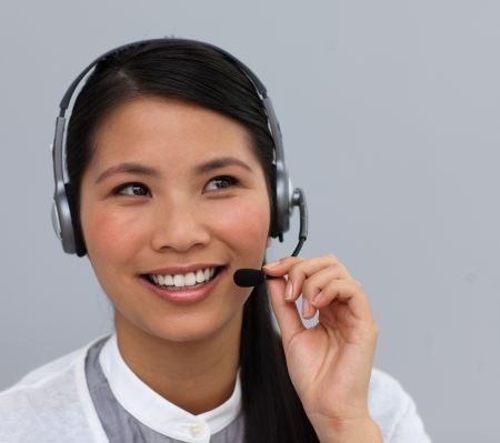 Smiling ethnic customer service talking on a headset photo