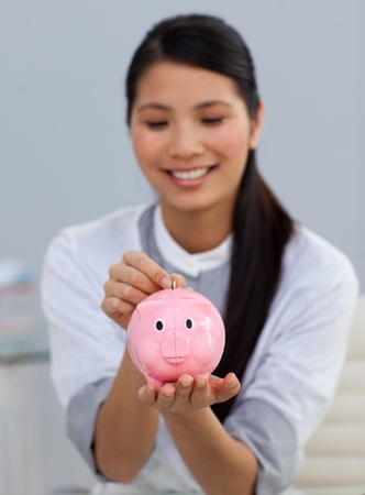 Smiling businesswoman saving money in a piggy bank  photo