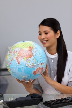 Smiling asian businesswoman looking at a globe  photo