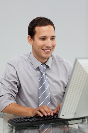 Charming young businessman working at a computer  photo
