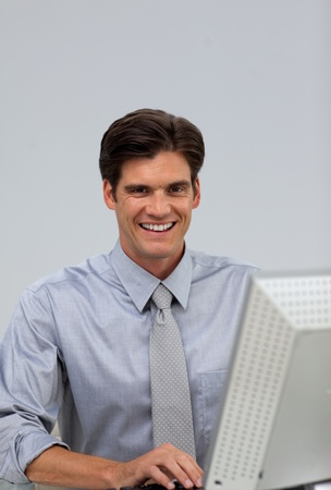 Cheerful businessman working at a computer  photo