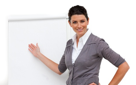 Confident female executive pointing at a board  Stock Photo - 10075716