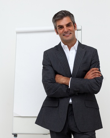 Businessman with folded arms in front of a board photo