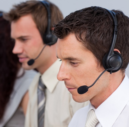 computer support: Portrait of an attractive man working in a call center