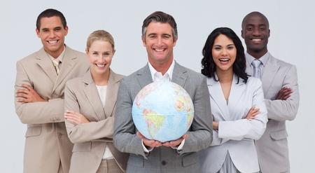 negocios internacionales: Equipo de negocios sosteniendo un globo terrestre