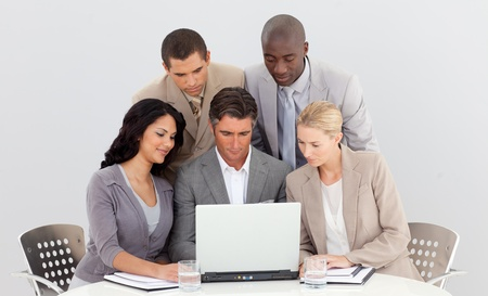 Multi-ethnic business team working with a laptop together photo