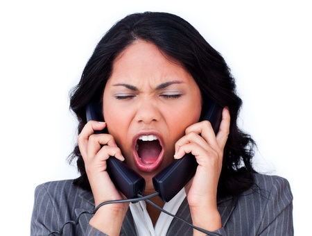 Frustrated businesswoman tangled up in phone wires  photo