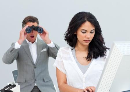 Charismatic businessman looking his colleagues computer through binoculars photo