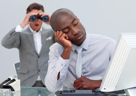 Asleep businessman annoyed by a man looking through binoculars photo