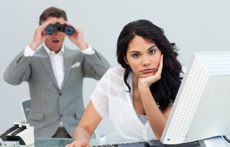 afflict: Brunette businesswoman annoyed by a man looking through binoculars