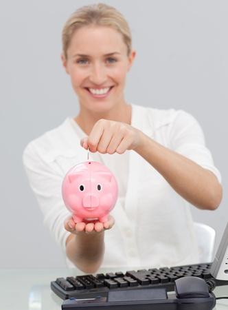 Smiling businesswoman saving money in a piggibank photo