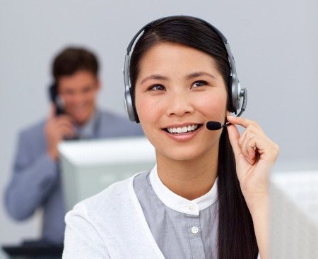 sales assistant: Young asian businesswoman with headset on at her desk Stock Photo