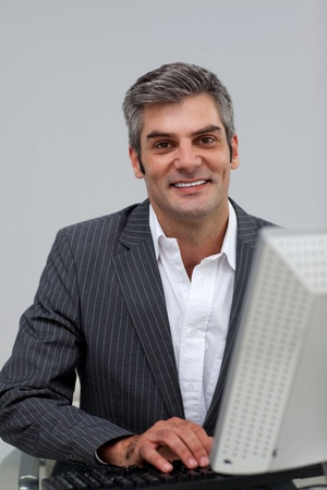 Self-assured male executive working at a computer  photo