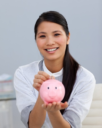 Charming asian businesswoman saving money in a piggybank photo
