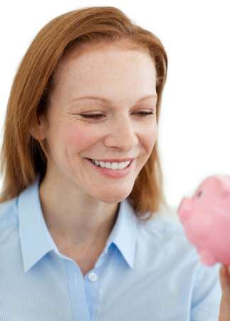 Young businesswoman saving money in a piggy bank photo