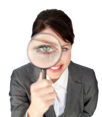 Close-up of a businesswoman looking through magnifying glass photo