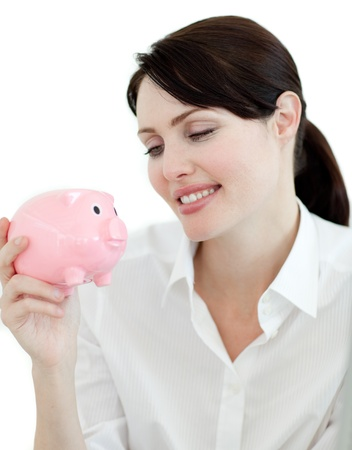 Attractive businesswoman looking at a piggybank photo