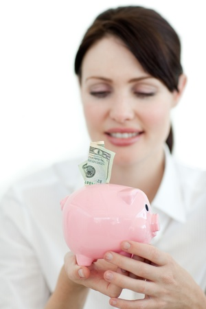 Young businesswoman saving money in a piggybank photo