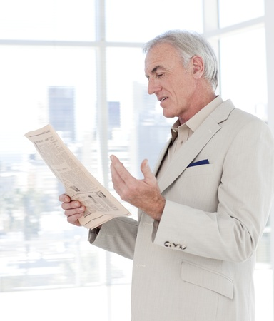 more mature: Portrait of a mature manager reading newspaper
