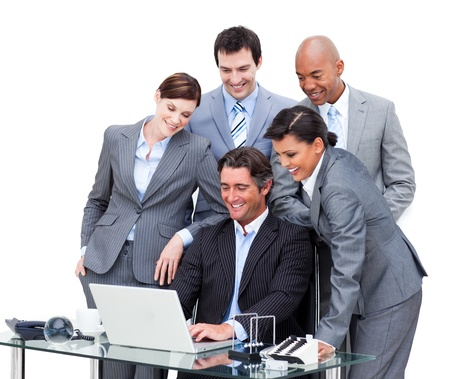 Cheerful international business team looking at a laptop Stock Photo - 10089656