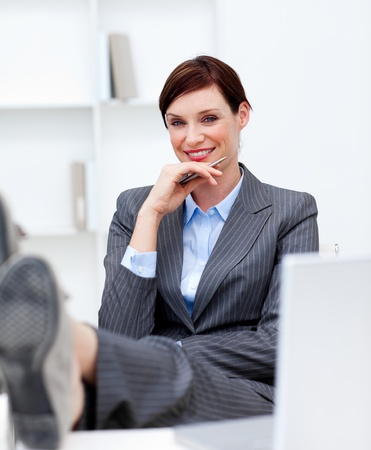 Attractive businesswoman leaning feet on desk  photo
