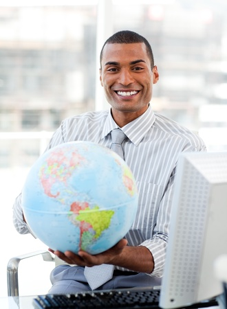 Ethnic businessman holding a terrestrial globe photo