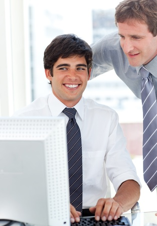 businessman working at his computer: Charming businessman working at a computer with his manager