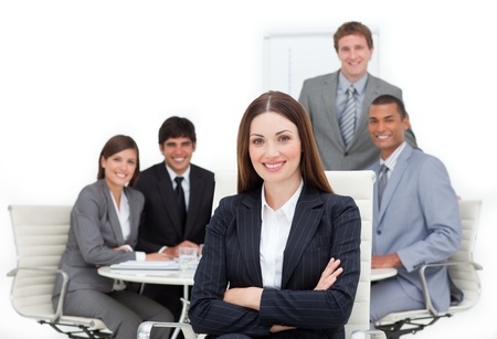 Charismatic female executive sitting in front of her team photo