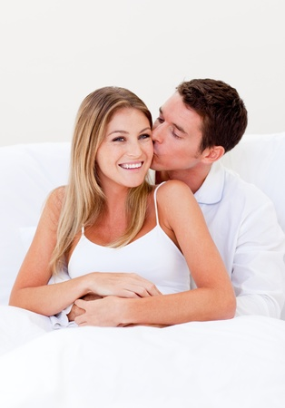 Affectionate man kissing his wife sitting on bed Stock Photo