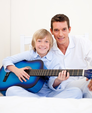 Merry little boy playing guitar with his father Stock Photo - 10091109
