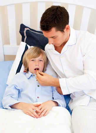 keep watch over: Affectionate father checking his sons temperature Stock Photo