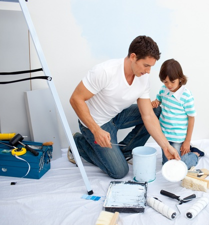 Father and his son painting in their new house  photo
