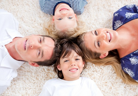 girl lying: Cheerful family lying in circle on the wall-to-wall carpet Stock Photo