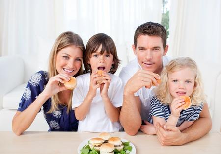 ni�os contentos: Familia entusiasta comer hamburguesas en la sala de estar
