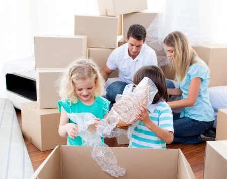 cardboard house: Animated family packing boxes Stock Photo