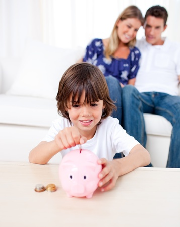 Joyful little boy inserting coin in a piggybank in the living room photo