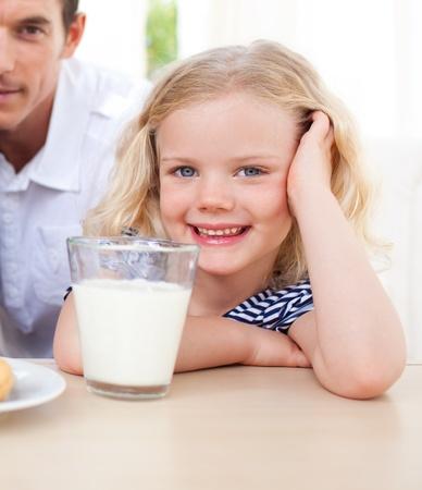 Smiling little girl drinking milk photo