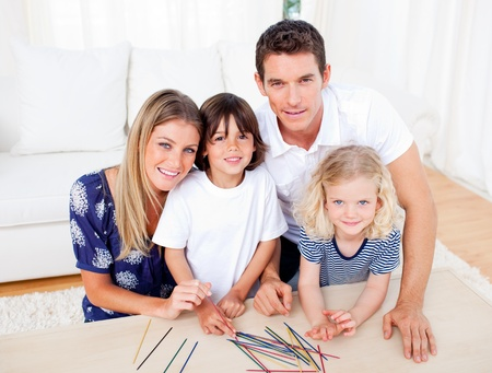 Cheerful family playing mikado in the living room Stock Photo - 10091257