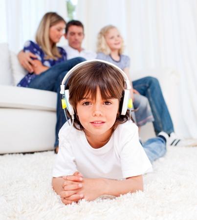 Cute little boy listening music lying on floor photo
