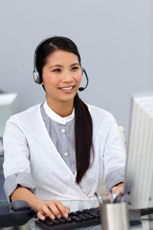 Smiling businesswoman working at a computer photo