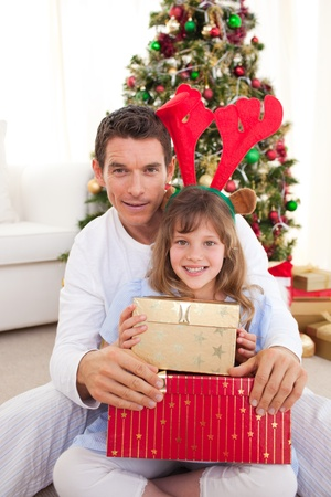 Portrait of a father and his daughter holding Christmas presents photo