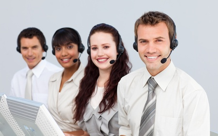 Smiling people with a headset on working in a call center photo