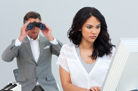 Ambitious businessman looking her colleagues computer through binoculars photo
