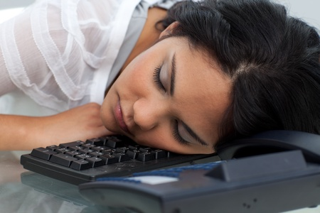 Young businesswoman sleeping on the keyboard photo