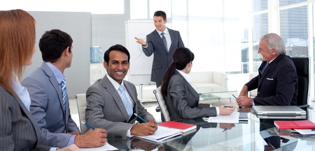 Businessman reporting sales figures to his team photo