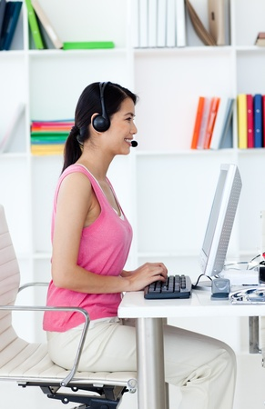Serious businesswoman with headset on at a computer photo
