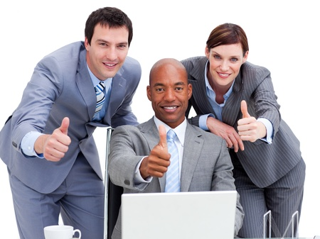 teaming: Business people with thumbs up looking at a laptop