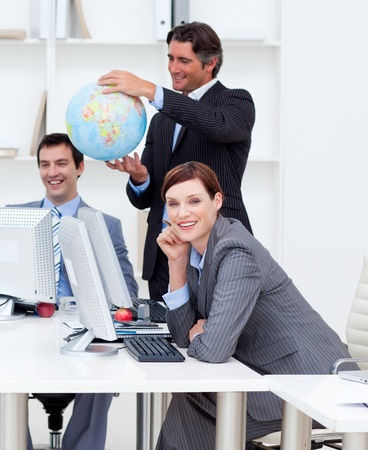 teaming: Happy manager holding a globe with his team working at computers